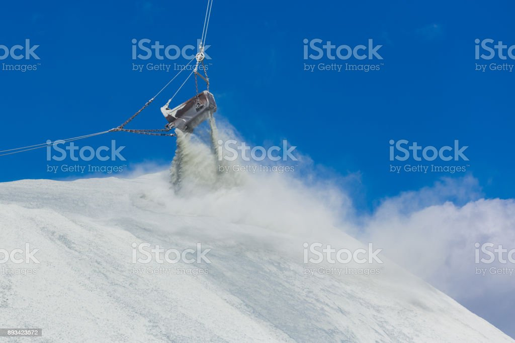 The bucket of the large quarry excavator is dumping waste products into the dumps stock photo