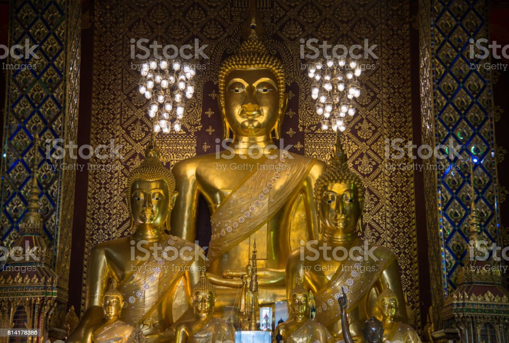 The Buddha statue in viharn of Wat Phra That Hariphunchai the iconic famous temple in Lamphun city, Northern Thailand. stock photo