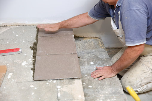 1167393641 istock photo The builder arranges ceramic tiles on the stairs inside the building. 1129836187
