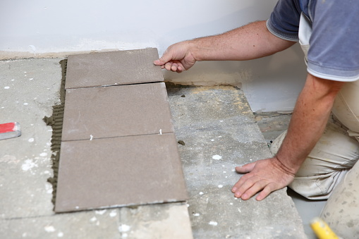 1167393641 istock photo The builder arranges ceramic tiles on the stairs inside the building. 1129836211