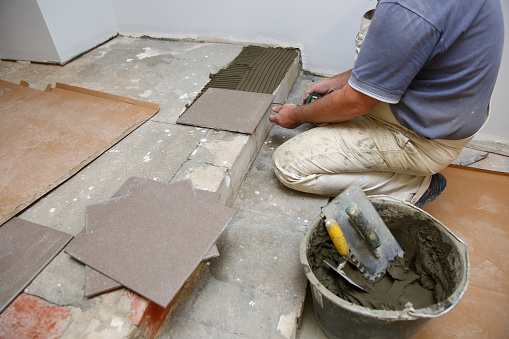 1167393641 istock photo The builder arranges ceramic tiles on the stairs inside the building. 1129836653