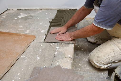 1167393641 istock photo The builder arranges ceramic tiles on the stairs inside the building. 1129836700