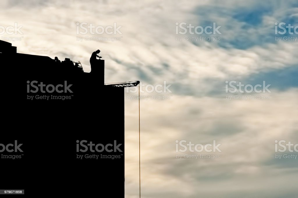 The builder at the construction site works at sunset The builder at the construction site works at sunset, at dawn Adult Stock Photo