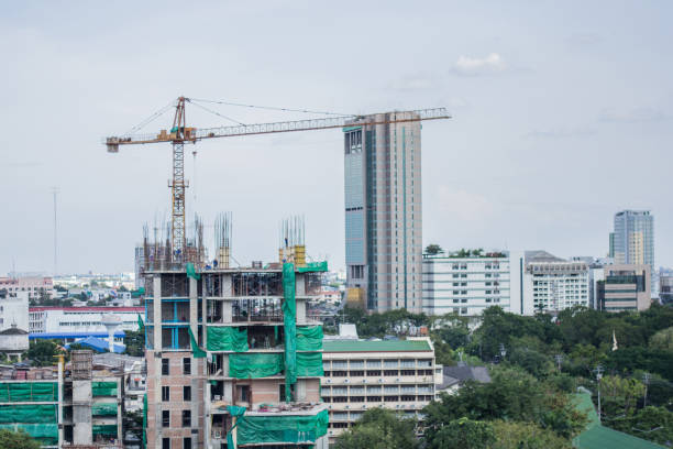 The building is under construction and has cranks on it,Workers are building stock photo