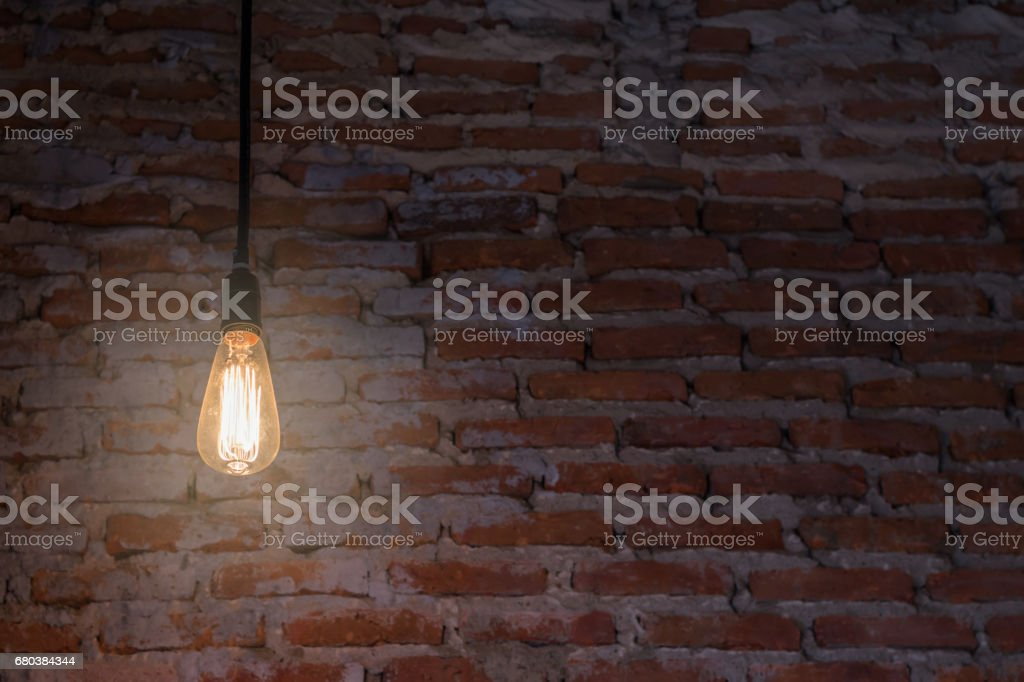 The bulb illuminated in the dark with brick background royalty-free stock photo
