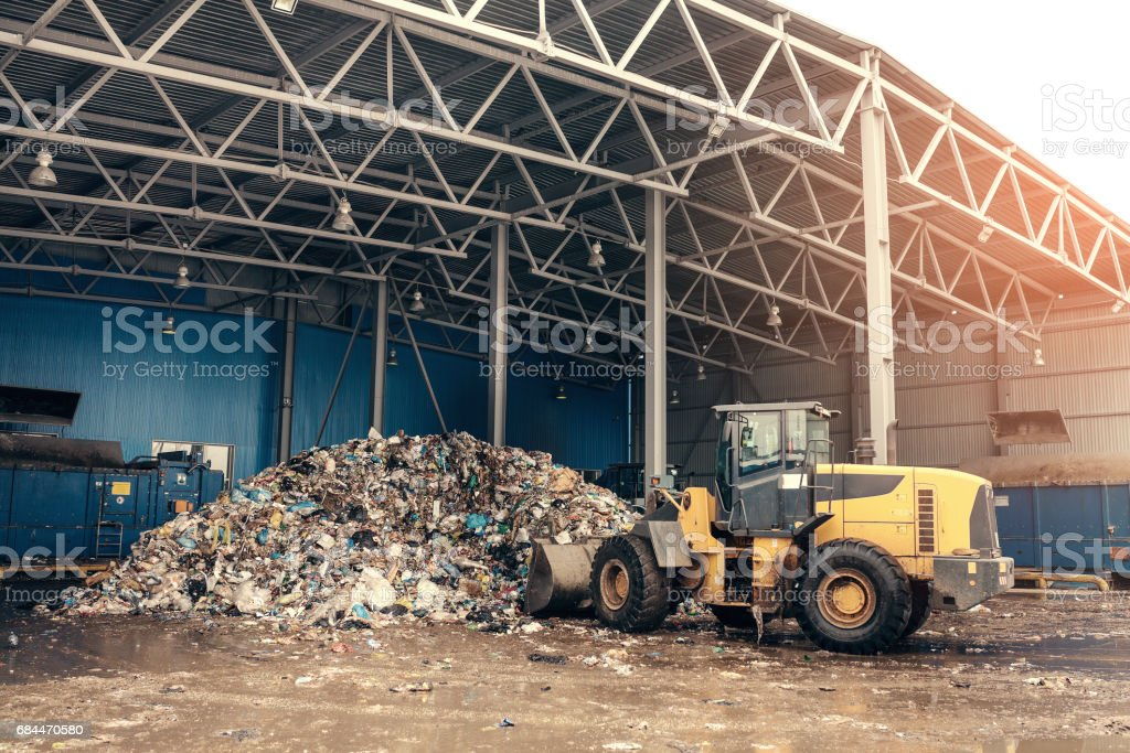 The bulldozer will clean the waste dump. Waste processing plant. Technological process. Business for sorting and processing of waste. stock photo