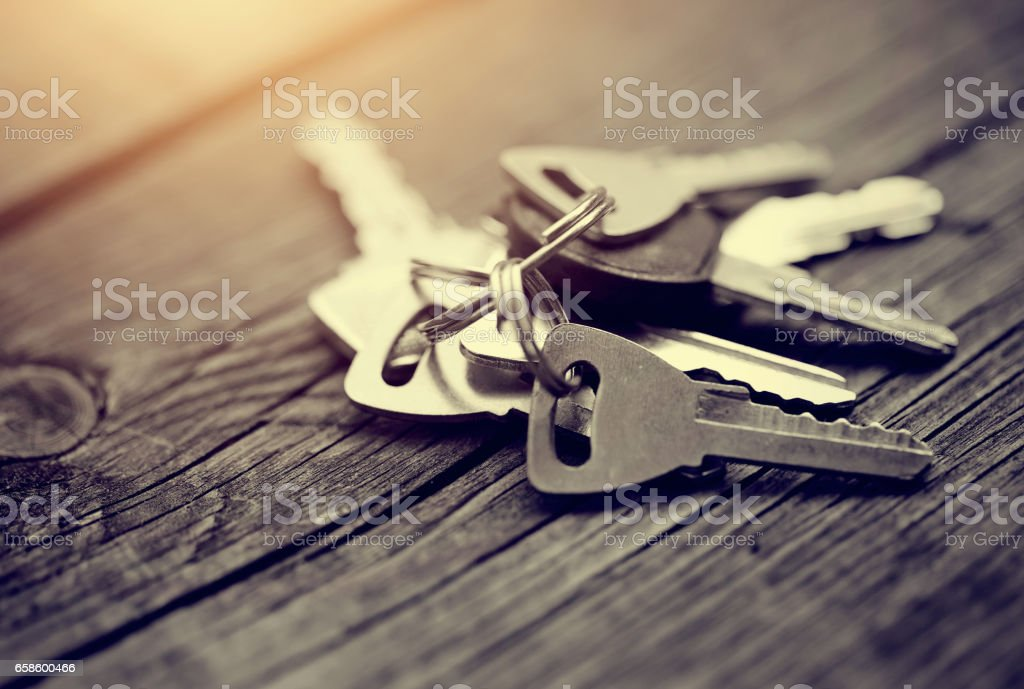 The bunch of keys on a wooden table. stock photo