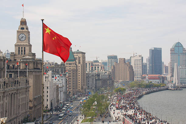 The Bund in Shanghai, China, with Chinese flag View of the historic Shanghai Financial District and Huangpu Riverfront huangpu river stock pictures, royalty-free photos & images