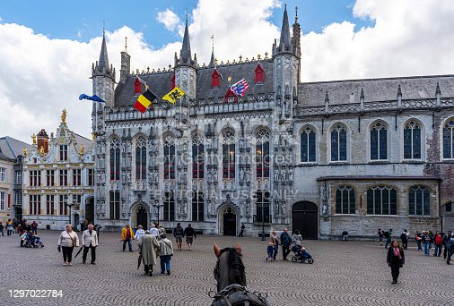Bruges, Belgium - July 2, 2016: Architectural ensemble in the Burg square with the City Hall and the Old Civil Registry ( Fietskoetsen ) and people walking in the medieval city of Bruges, Belgium.
