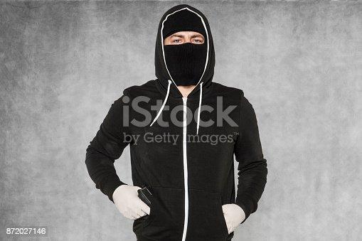 istock The burglar holds the gun in his pocket 872027146