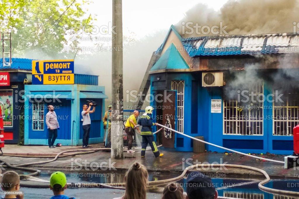 Das Verbrennen eines Ladens auf der Stadtstraße. Die Löscharbeiten. - Lizenzfrei Arbeiten Stock-Foto