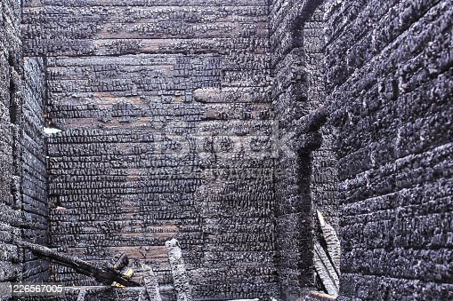 istock The burnt frame of the private village wooden house. Burnt wood texture. 1226567005