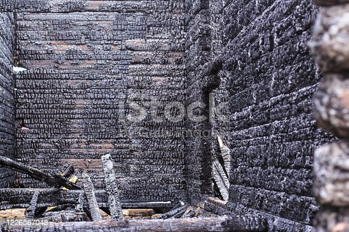 istock The burnt frame of the private village wooden house. Burnt wood texture. 1226567048