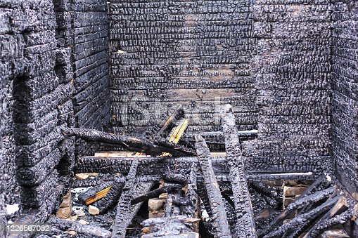 istock The burnt frame of the private village wooden house. Burnt wood texture. 1226567082