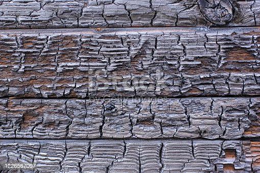 istock The burnt frame of the private village wooden house. Burnt wood texture. 1226567097
