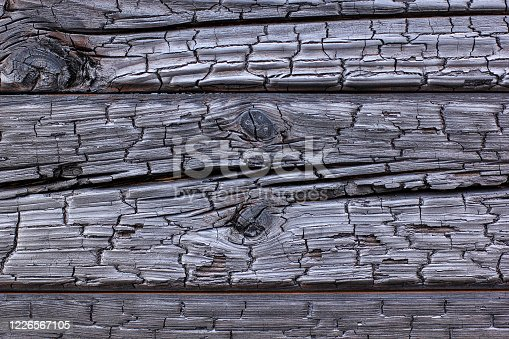 istock The burnt frame of the private village wooden house. Burnt wood texture. 1226567105