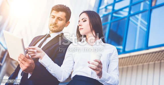 The business man and woman stand with a tablet on the background of the building