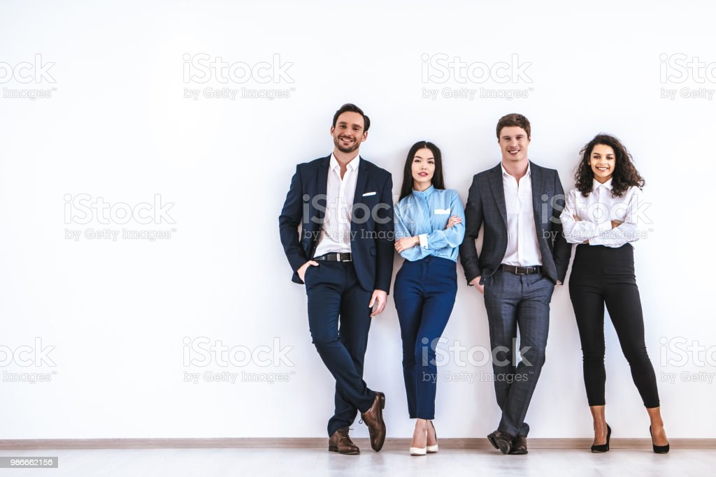 The business people standing on the white wall background - Royalty-free Adult Stock Photo