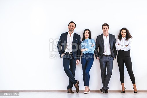 istock The business people standing on the white wall background 986662156
