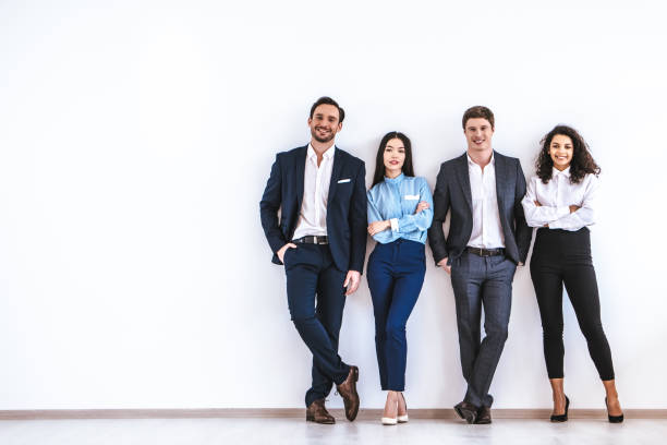 The business people standing on the white wall background The business people standing on the white wall background four people stock pictures, royalty-free photos & images