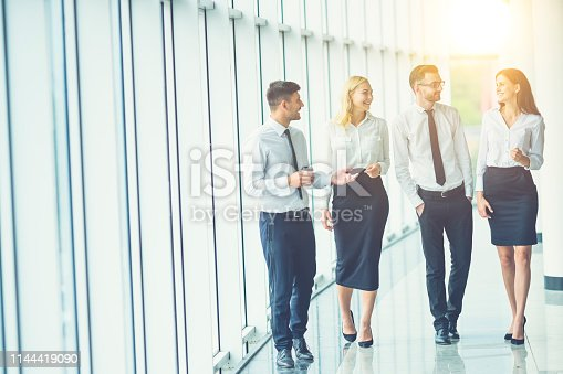The business people walk in the office hall on the sun background