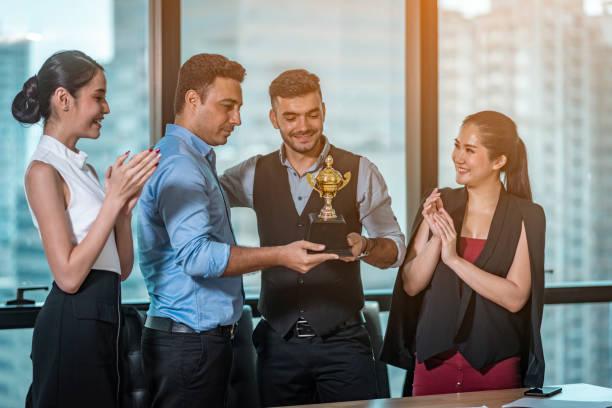 l'équipe d'affaires célèbre le trophée du travail. - cérémonie photos et images de collection
