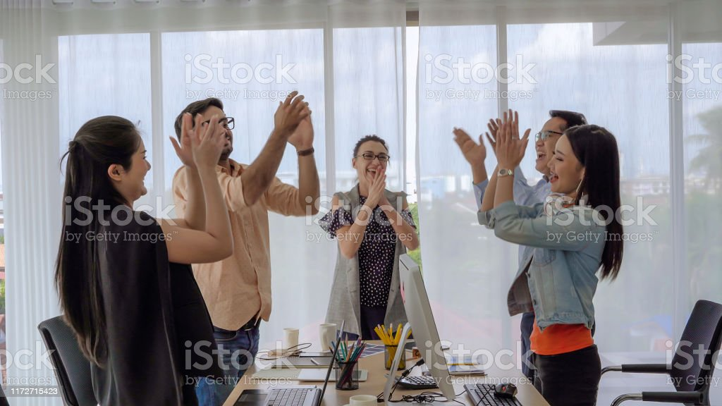The business team leader calls the team members to join hands to show...