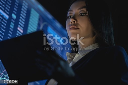 850852928 istock photo The business woman holding tablet in the dark office 1212375014