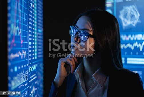 847519080 istock photo The business woman looks on a large blue screen with chart 1212374978