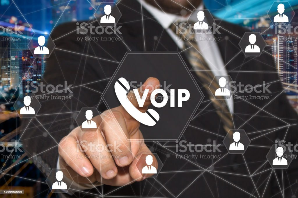The businessman chooses VOIP button on the touch screen with a futuristic background .The concept  VOIP. The businessman chooses VOIP button on the touch screen with a futuristic background .The concept  VOIP. Adult Stock Photo