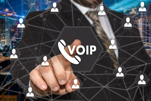 The Businessman Chooses Voip Button On The Touch Screen With A Futuristic Background The Concept Voip Stock Photo - Download Image Now