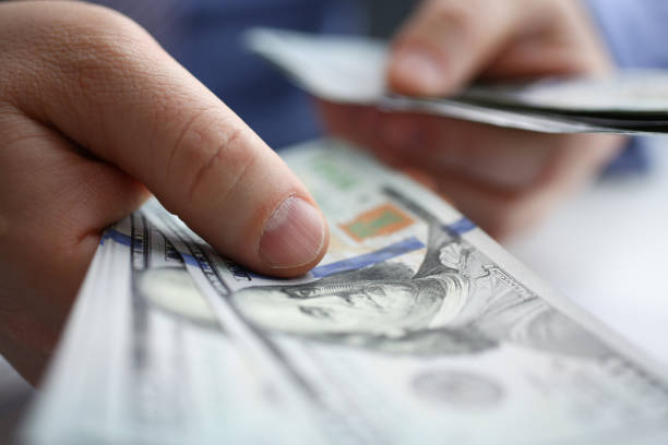 the businessman considers cash dollars in the office - depositor stock pictures, royalty-free photos & images