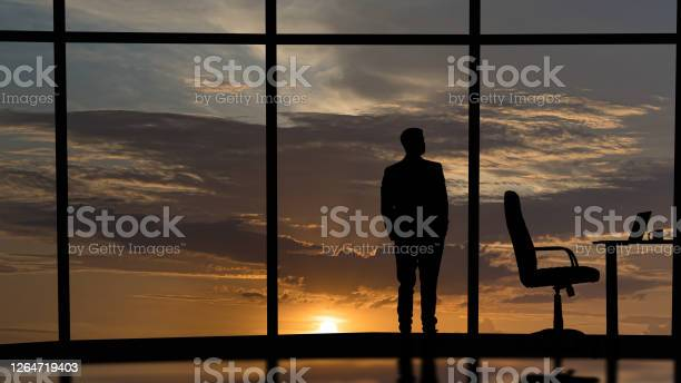 Photo of The businessman is standing near the windows in the office center