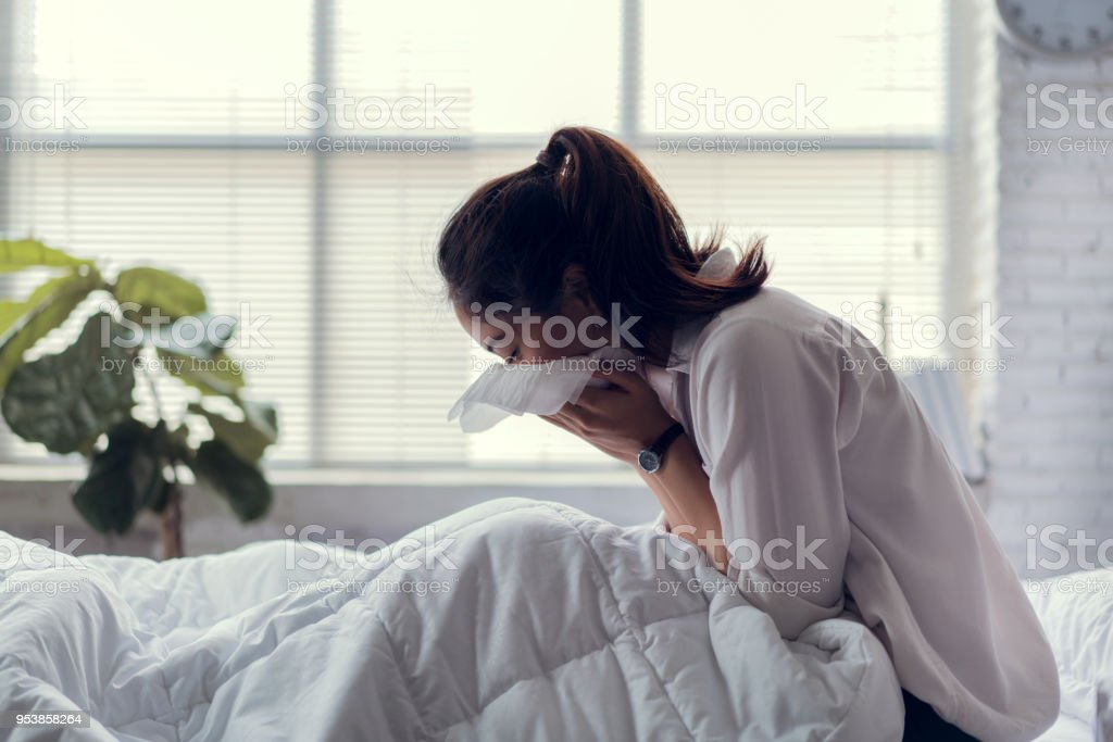 The businessman is unable to work, she is sick and sneezing heavily in bed. stock photo