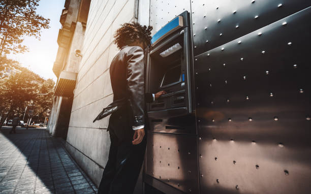 The businessman is using street ATM Wide-angle view of a curly businessman in a formal suit using an outdoor cash dispenser to increase his account; man entrepreneur is withdrawing money using a street ATM in urban settings banks and atms stock pictures, royalty-free photos & images