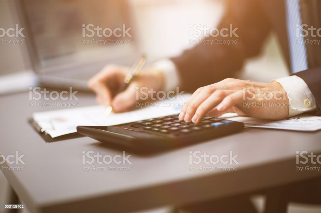 The businessman makes his own accounting, a financial report using a calculator stock photo