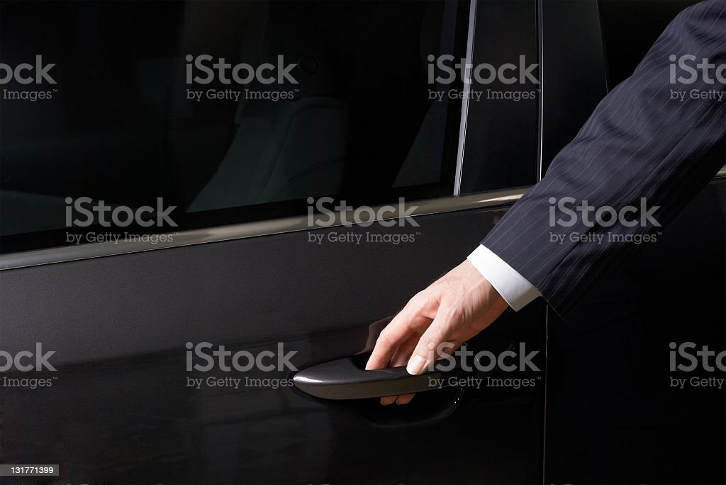 The businessman opens a door of the car stock photo
