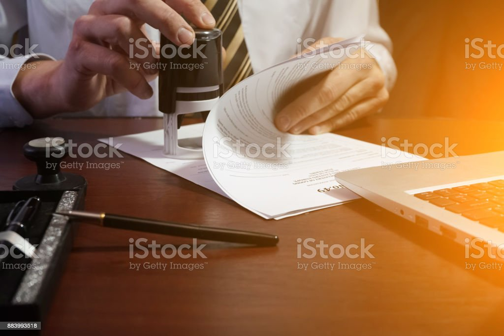 The businessman puts a stamp on the contract stock photo