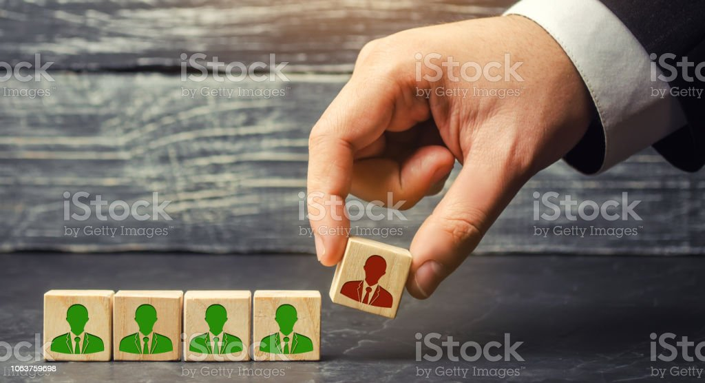the businessman removes / dismisses the employee from the team. management within the team. wooden blocks with a picture of workers. control arm. leader. resignation stock photo