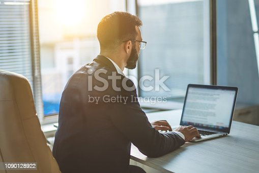 istock The businessman sitting at the table with a modern laptop 1090128922