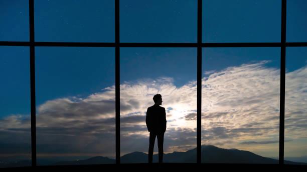 the businessman standing near the panoramic window on blue sky background - man look sky scraper foto e immagini stock
