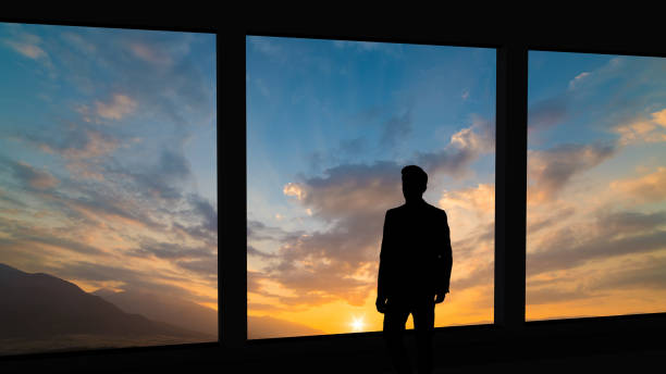 the businessman standing near the panoramic window on the  sunset background - man look sky scraper foto e immagini stock