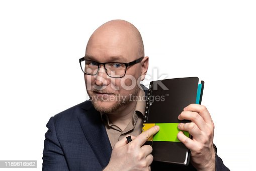 951331990 istock photo The businessman with a sly smile points to the cover of the diary 1189616562
