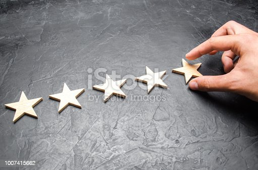istock The businessman's hand in the suit holds the fifth star. Get the fifth star. The concept of the rating of hotels and restaurants, the evaluation of critics and visitors. Quality level, good service. 1007415662