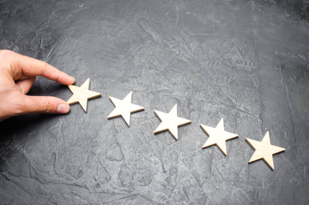 The businessman's hand in the suit holds the fifth star. Get the fifth star. The concept of the rating of hotels and restaurants, the evaluation of critics and visitors. Quality level, good service. stock photo