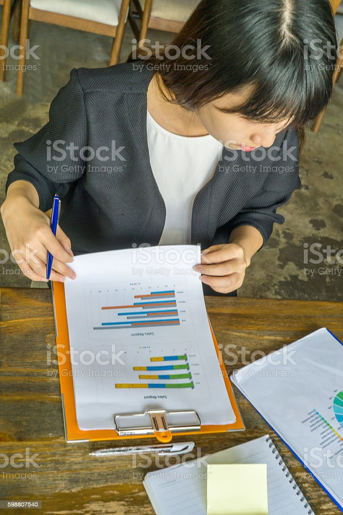 The businesswoman doing cross-check of data between two reports stock photo