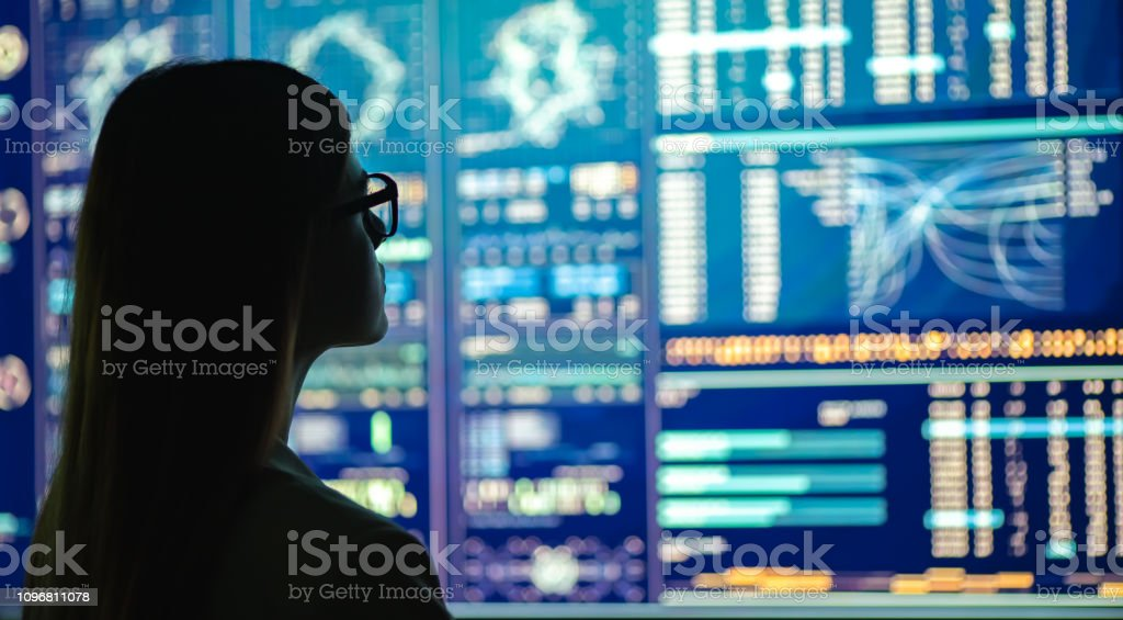 The businesswoman in glasses standing near the display The businesswoman in glasses standing near the display Adult Stock Photo