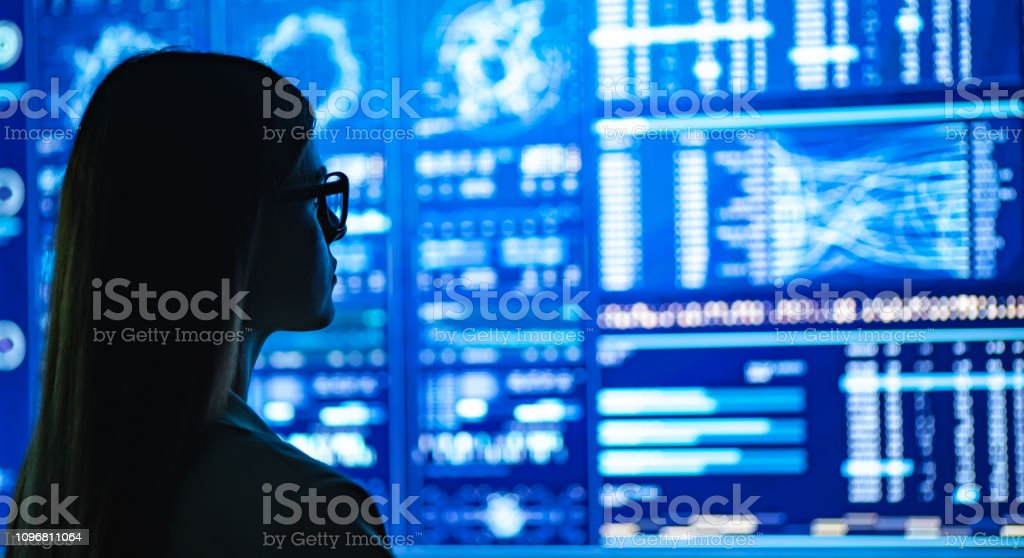 The businesswoman standing near the blue display The businesswoman standing near the blue display Adult Stock Photo