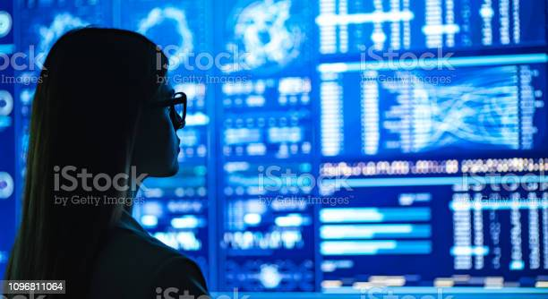 The Businesswoman Standing Near The Blue Display Stock Photo - Download Image Now