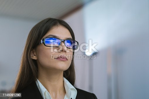 istock The businesswoman with glasses against the background of the projector 1145091290
